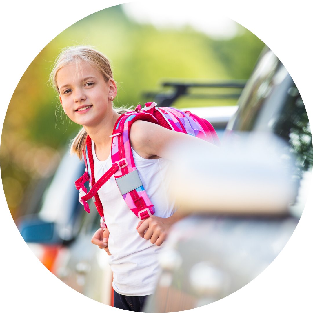 girl wearing backpack walking between cars