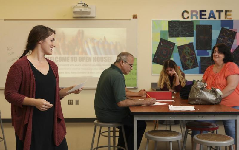 Art teacher talks with parents in classroom