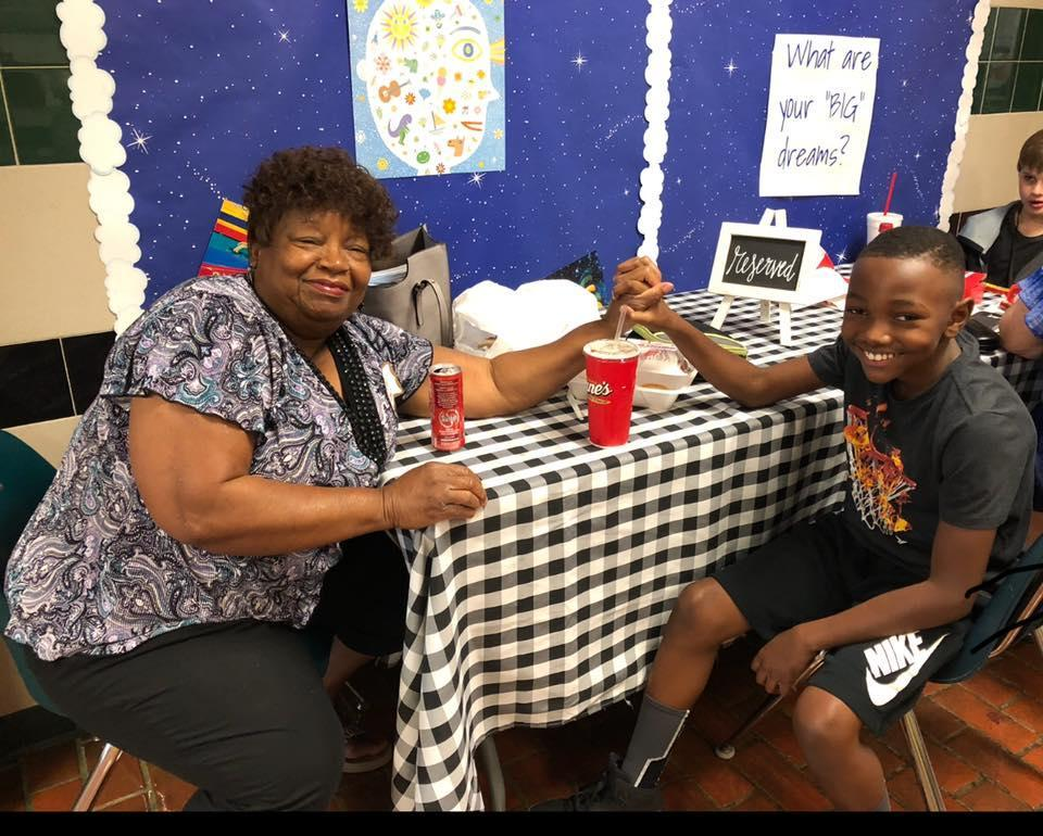 grandmother and grandson hold hands at the lunch table