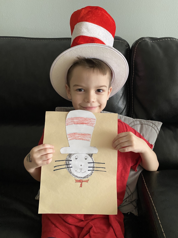 Boy wearing Cat in the Hat hat and holding drawing