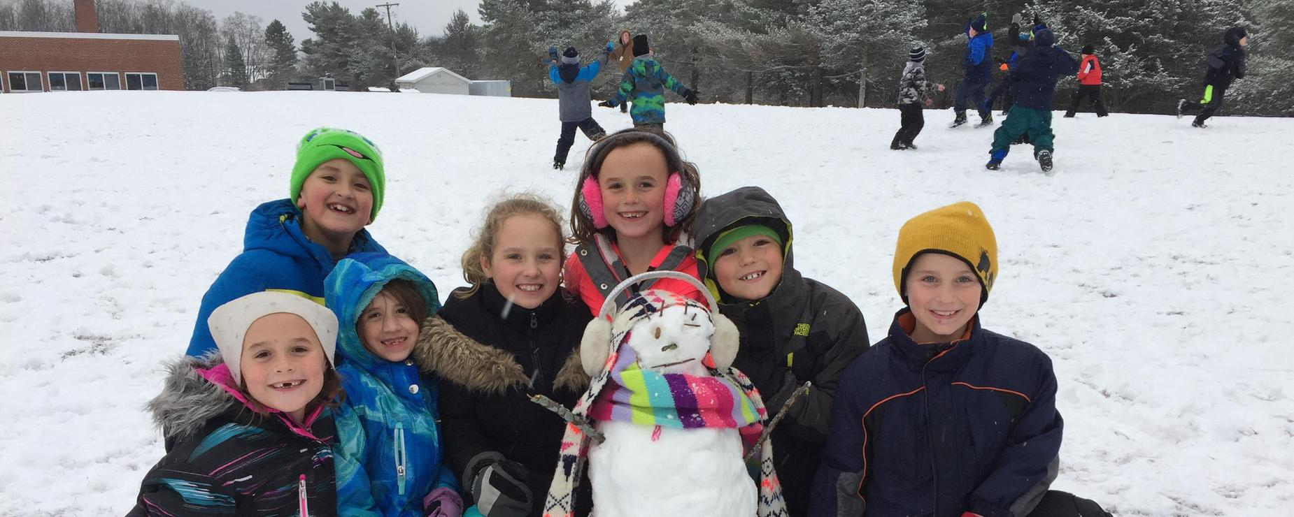 A group of students surround their snowman creation