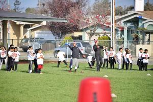 Students learn to throw a football.