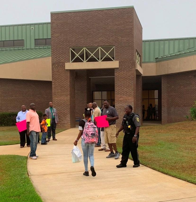 Community members welcome students on first day.