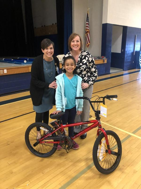 Photo of Mrs. Penny, Mrs. Barnes, and Peyton with the bike she won
