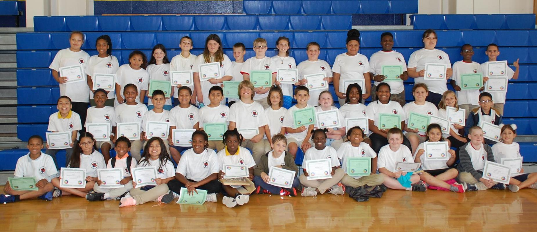 students holding certificates in front of bleachers in the gym