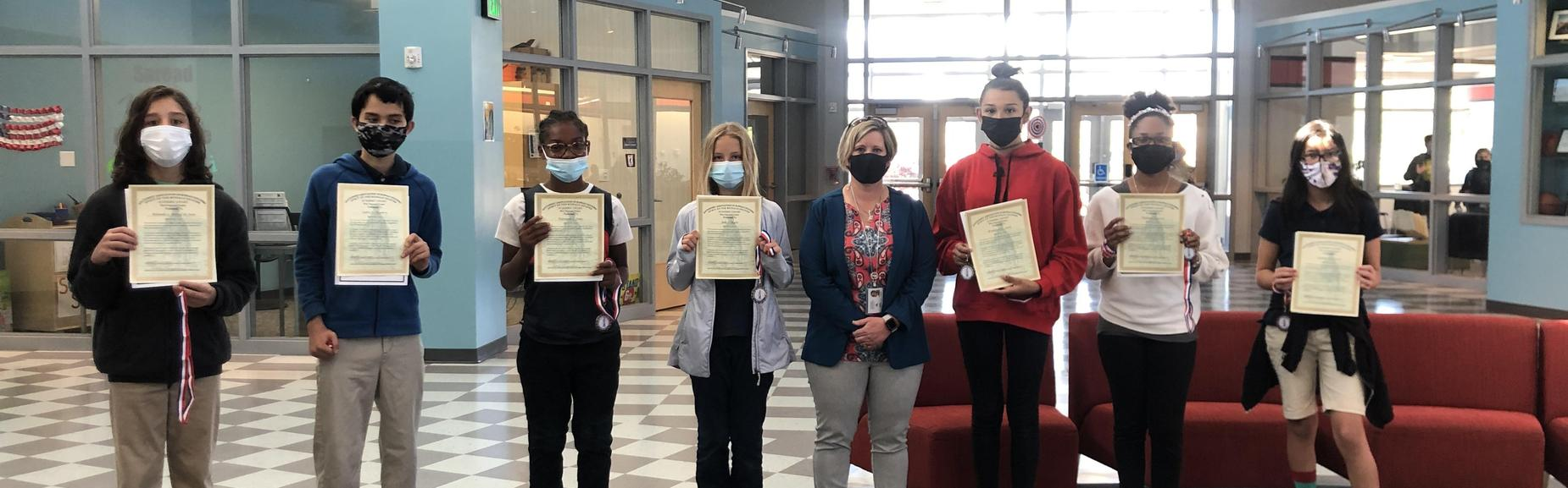 Eight people standing in line displaying award certificates.