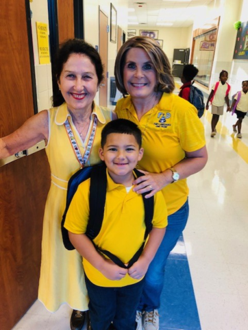 Two teachers with a student in All Yellow