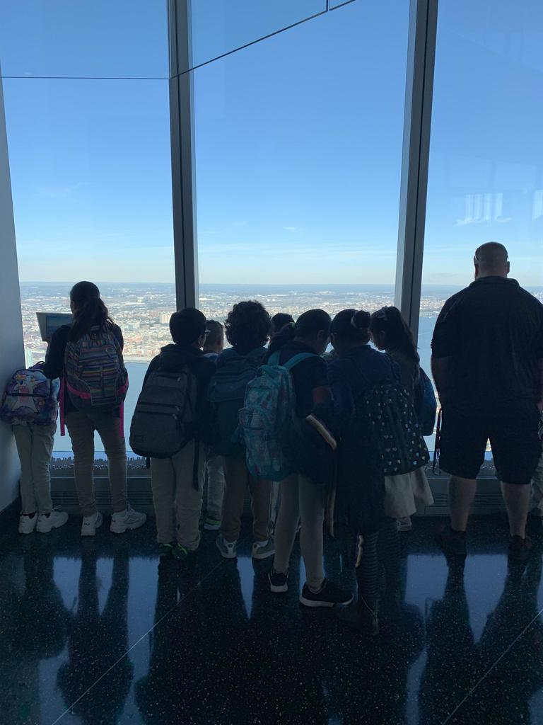 group of kids with Mr. Blake looking out at the NY Skyline with their ipads