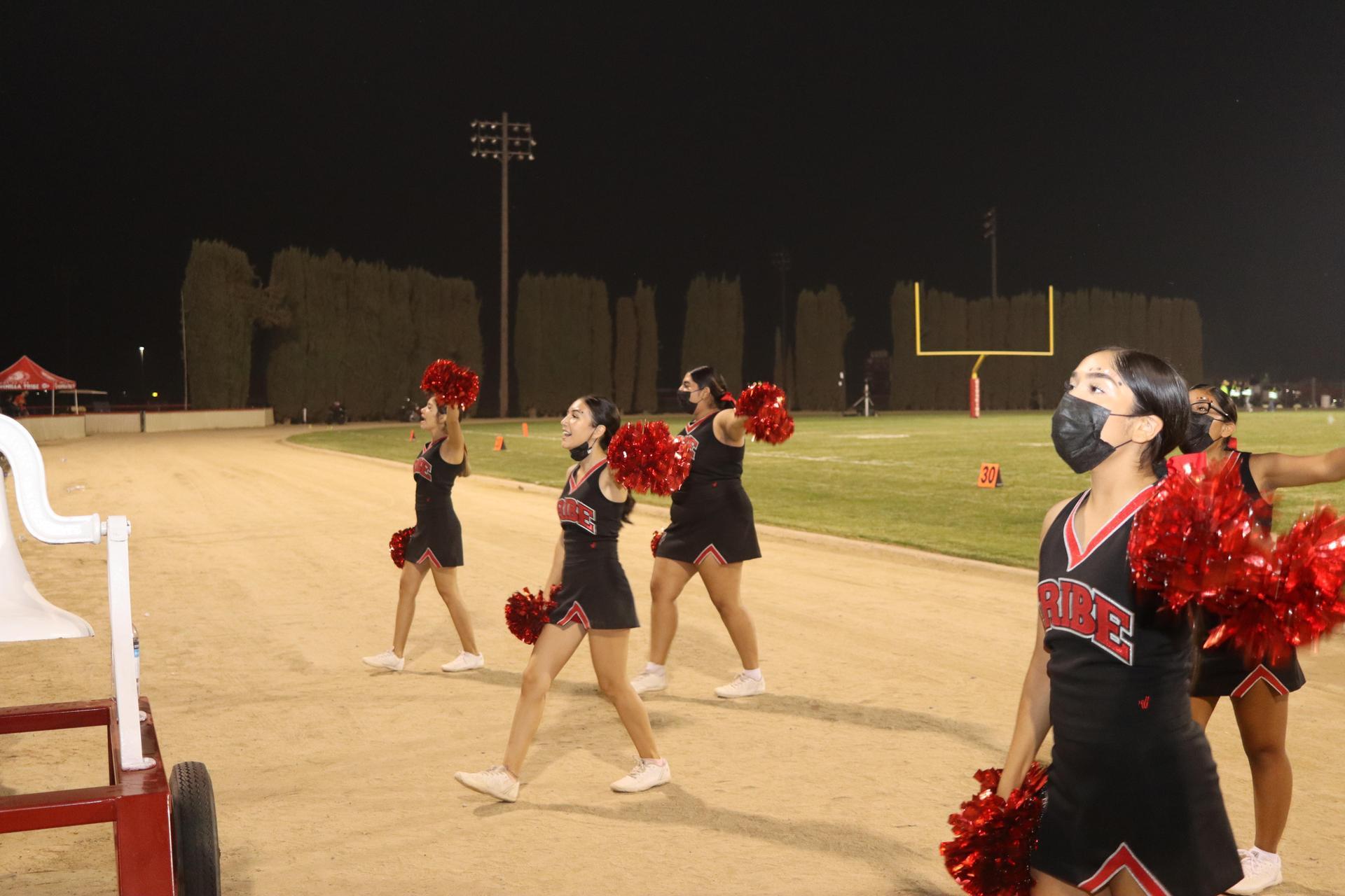 Varsity girls cheering at the football game against Lemoore