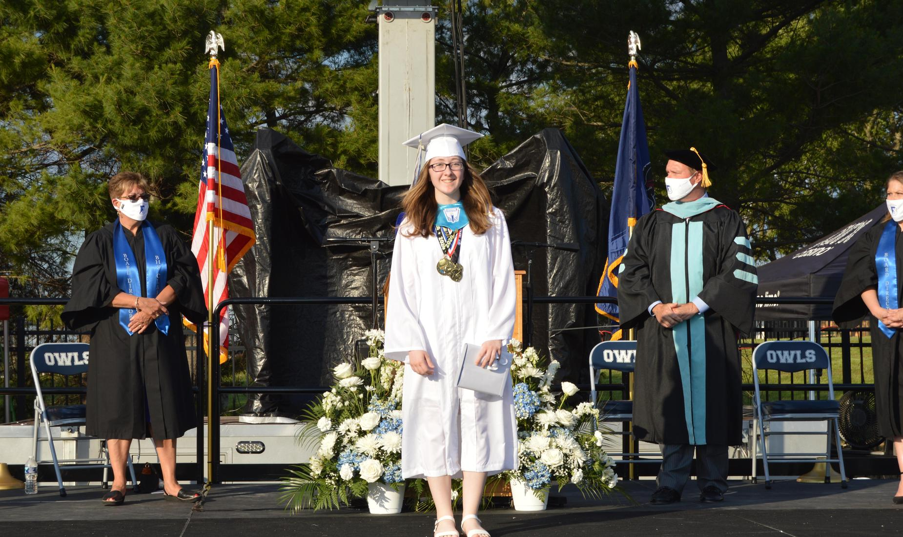 BHS Senior dresses in white graduation cap and gown poses on stage holding her diploma