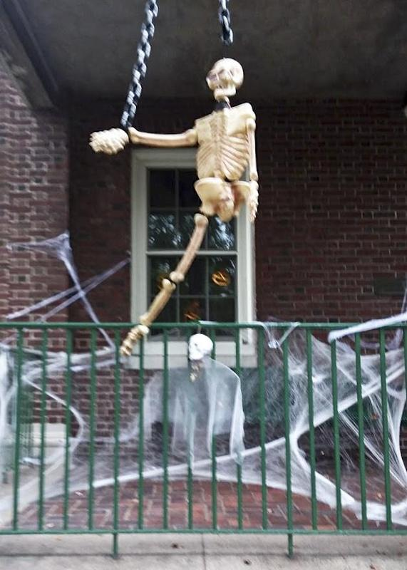 Chained manequin skeleton hangs suspended over porch rail.