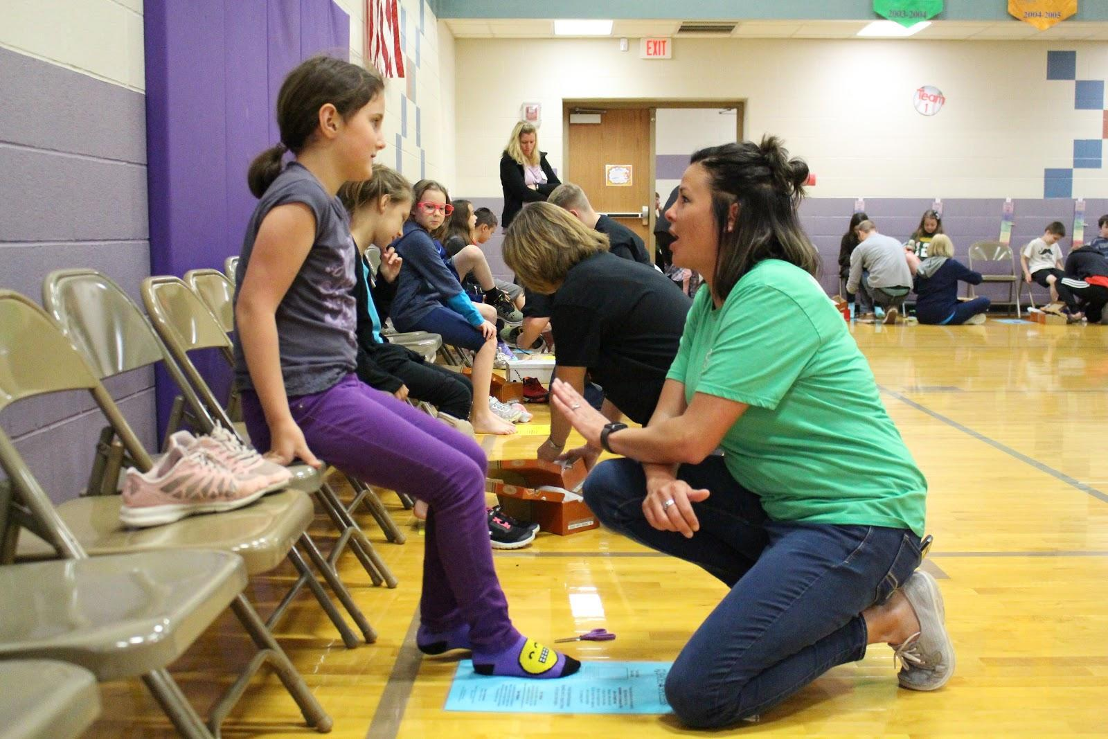 Preble County Success Liaison helping student try on shoes