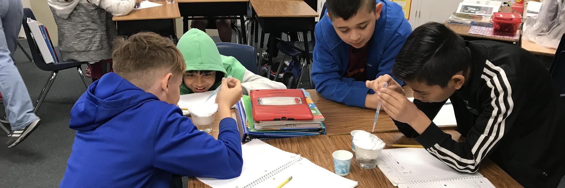 fifth graders doing a water cycle experiment