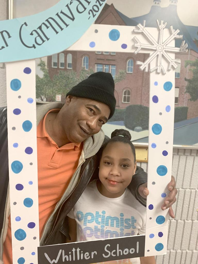 An adult and a student at the photo booth featuring a handmade, winter-themed frame