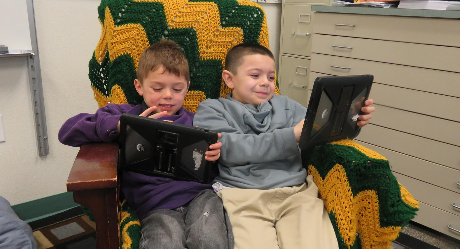 Two boys complete their work using an iPad while sitting in a soft easy chair.