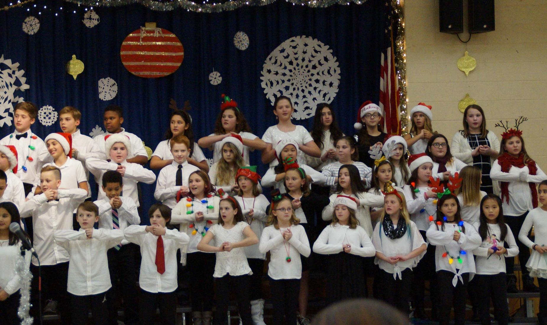 Girls and boys dressed on white tops and black pants, some with Santa hats, singing in the chorus