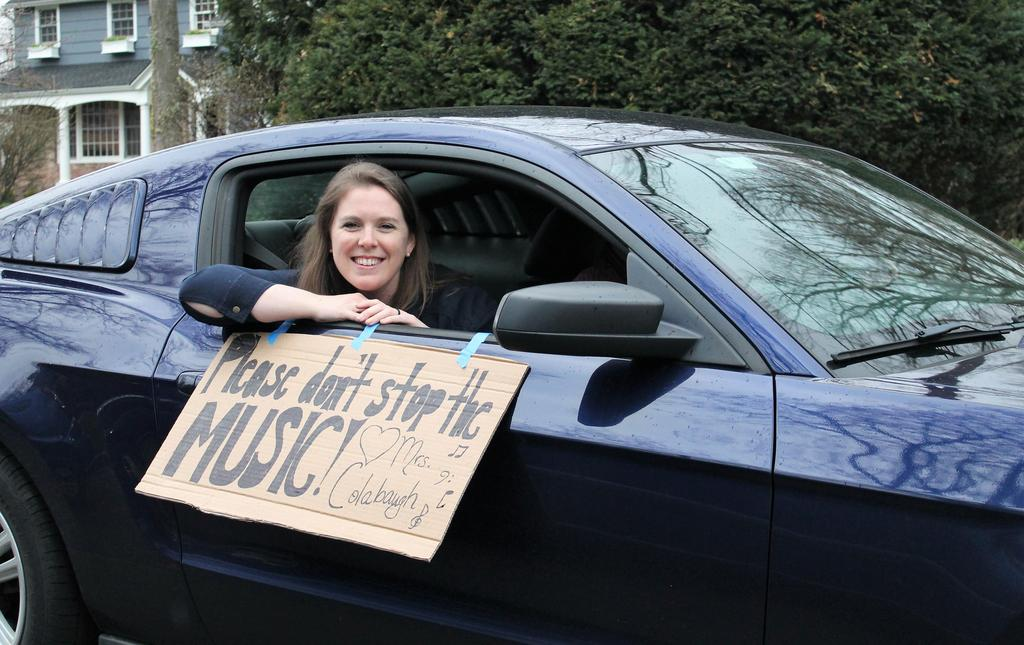 Photo of Washington teacher smiling with sign during car parade for students during COVID-19 distance learning.
