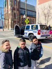 three boys smiling with the pd vehicle behind them