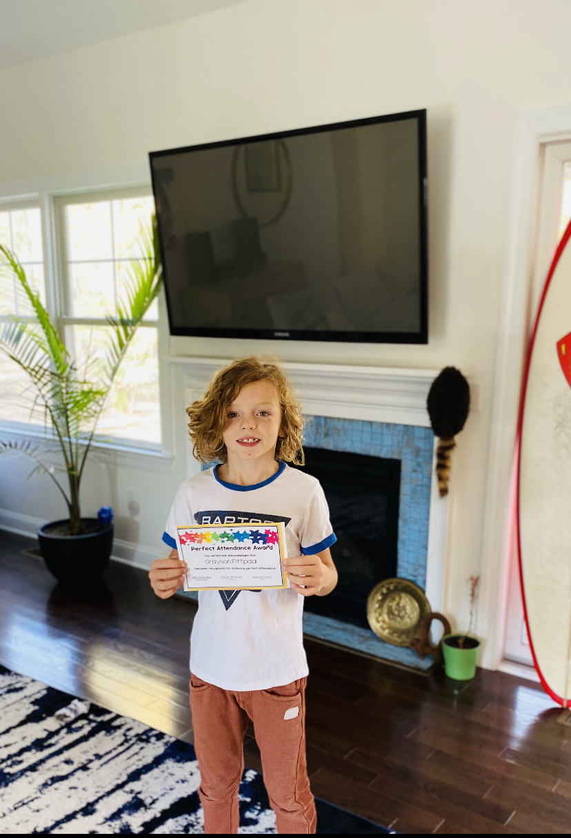 Grayson holding perfect attendance certificate