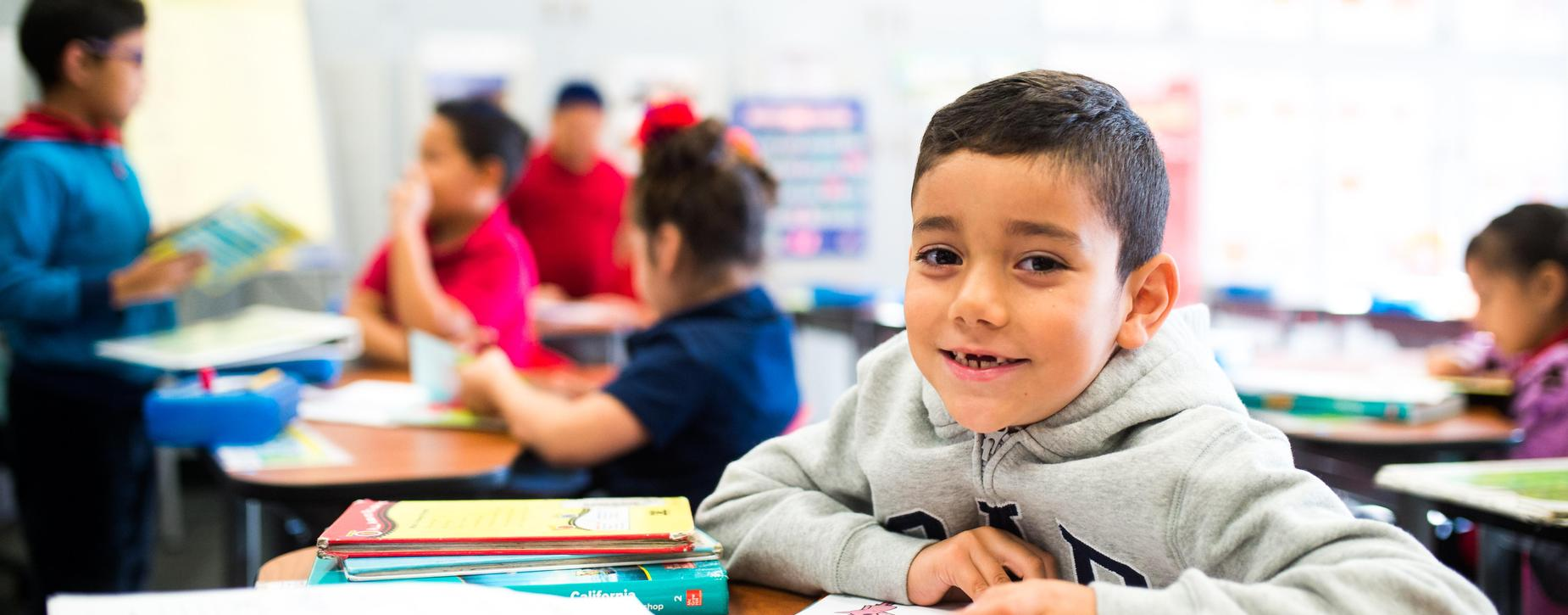 smiling boy at desk in classroom