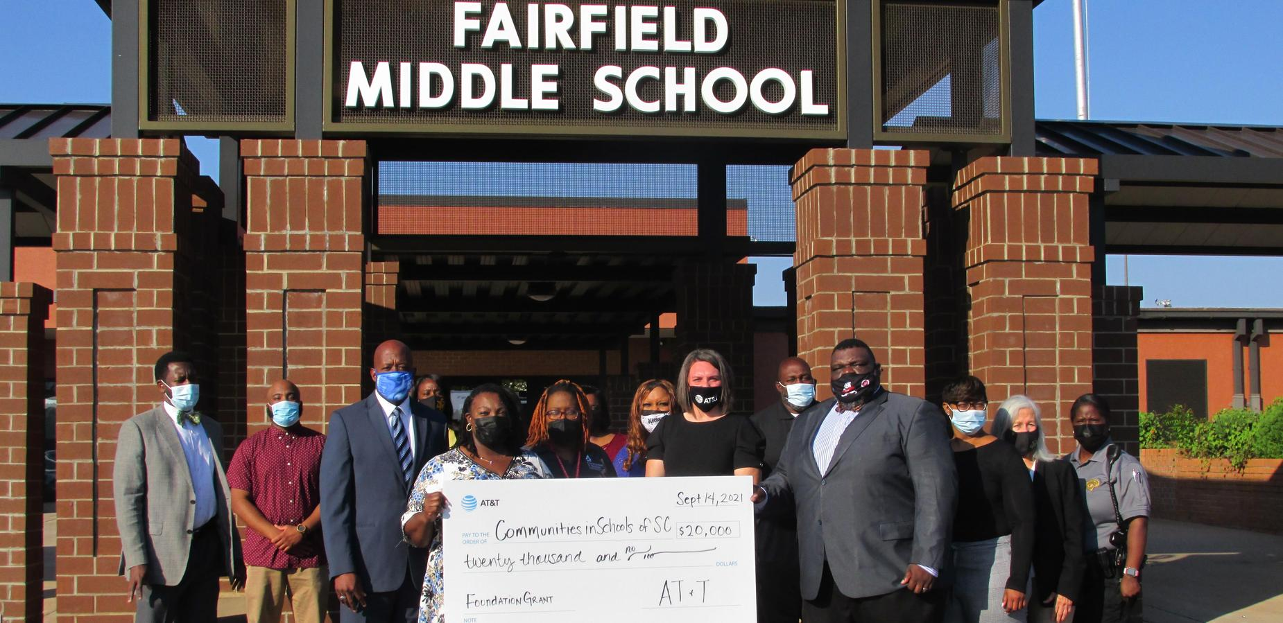 Communities in School giving check to FCSD