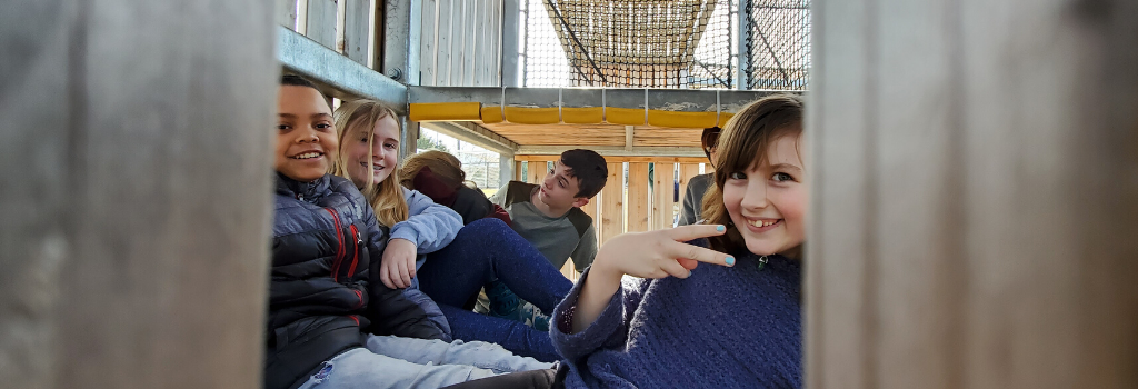 Students sitting inside Dragon's Rock play space