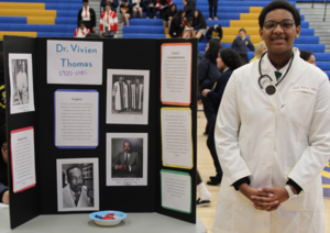 Teenage African American girl in lab coat standing next to a display board about Dr. Vivien Thomas