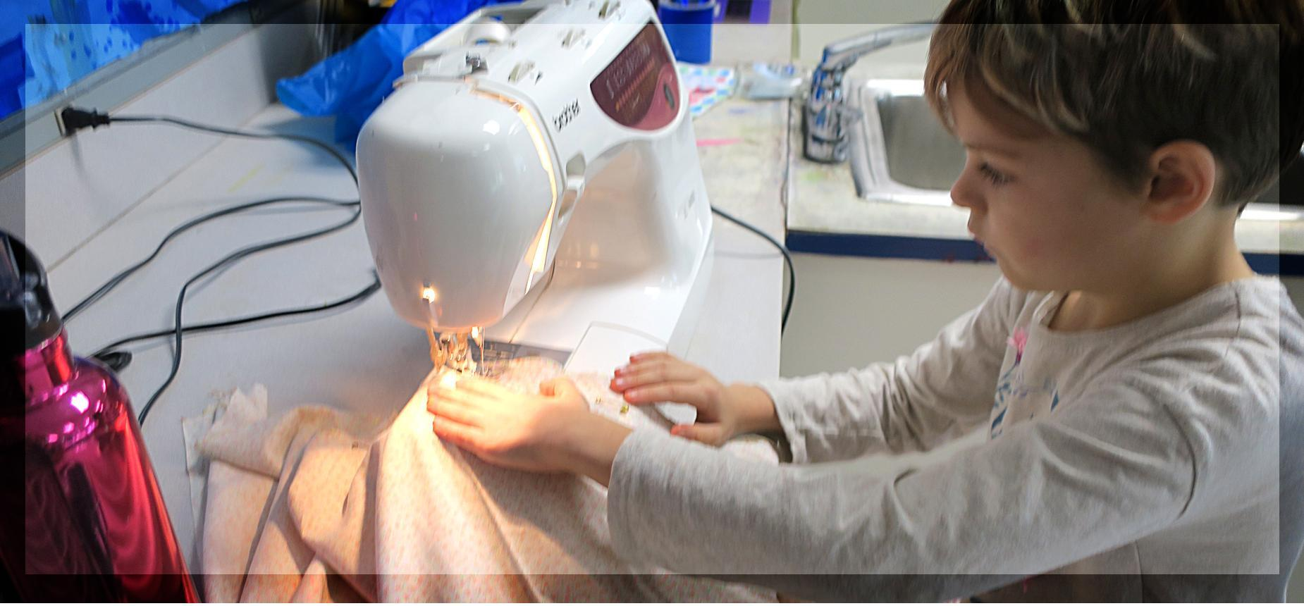 Elementary student learning how to sew on a sewing machine.