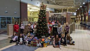 NHS kids around the tree with gifts