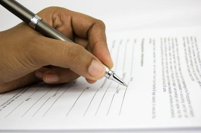 Hand holding a pen filling out a form