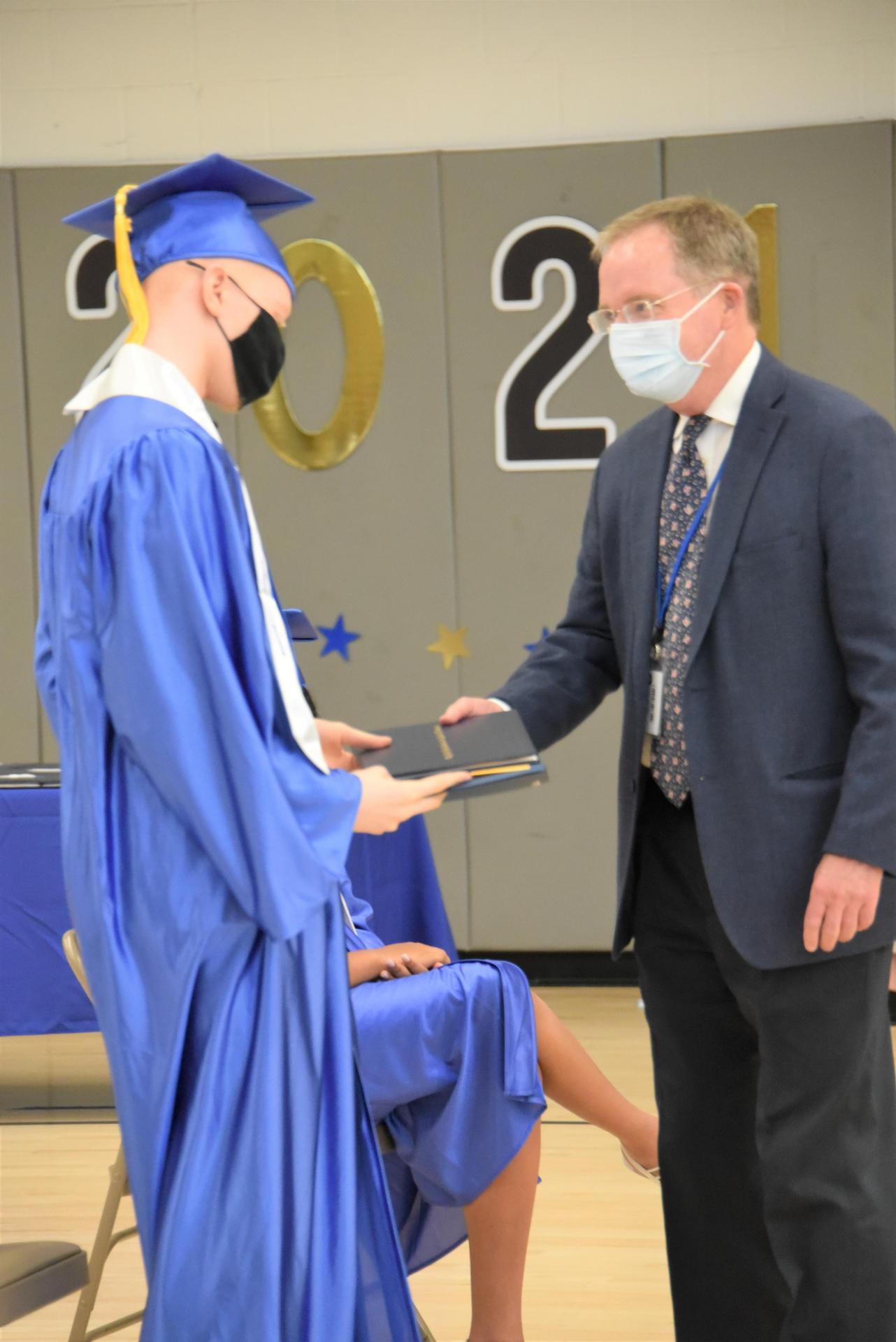 A student is handed a diploma at a graduation ceremony