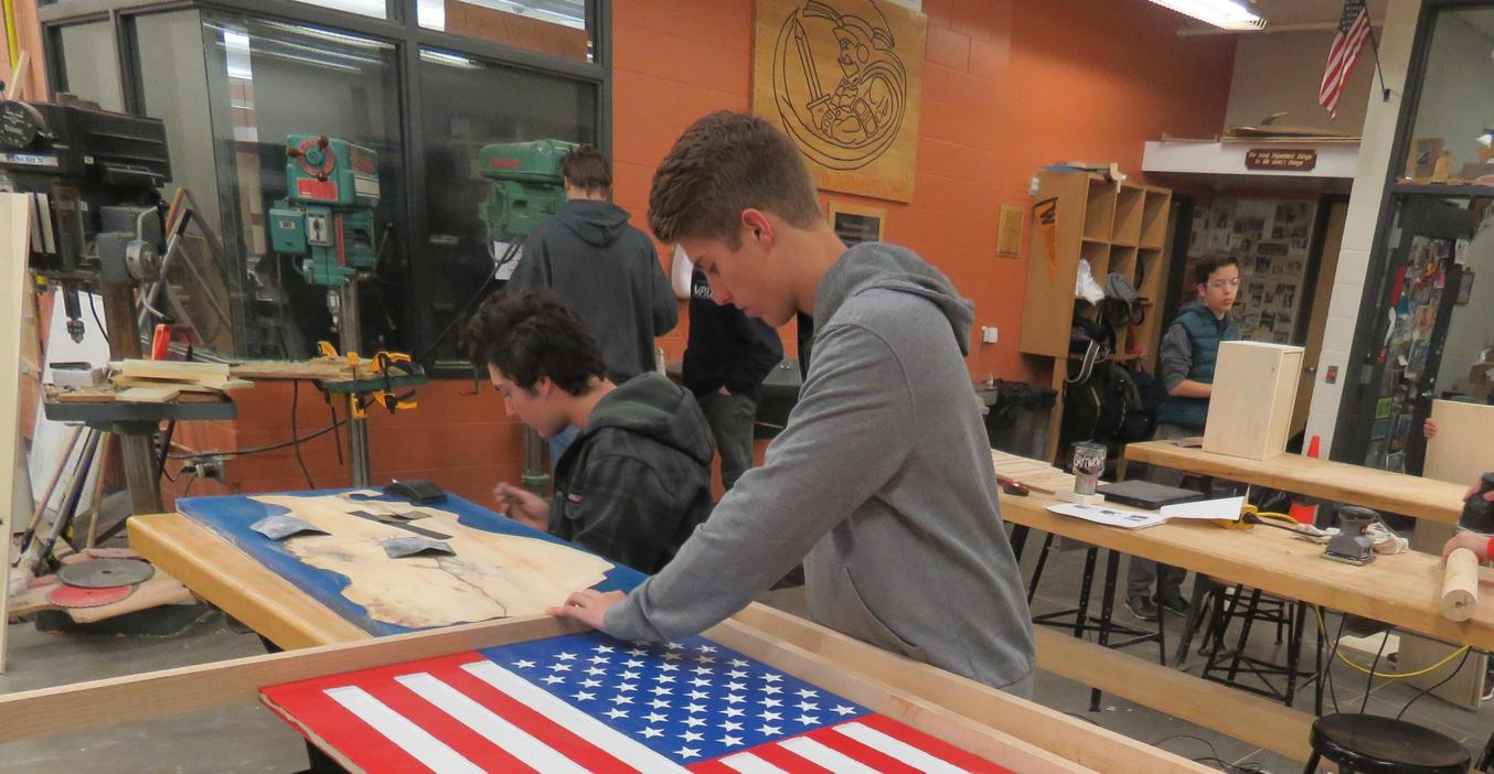 A TKHS woods  students works on finishing a patriotic table.