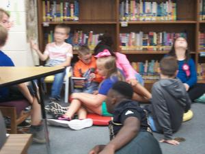 Students are reading with East Davidson football player.
