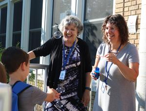 Staffer blows bubbles as she and Lincoln School principal Audrey Zavetz greet new kindergartners on first day of school.
