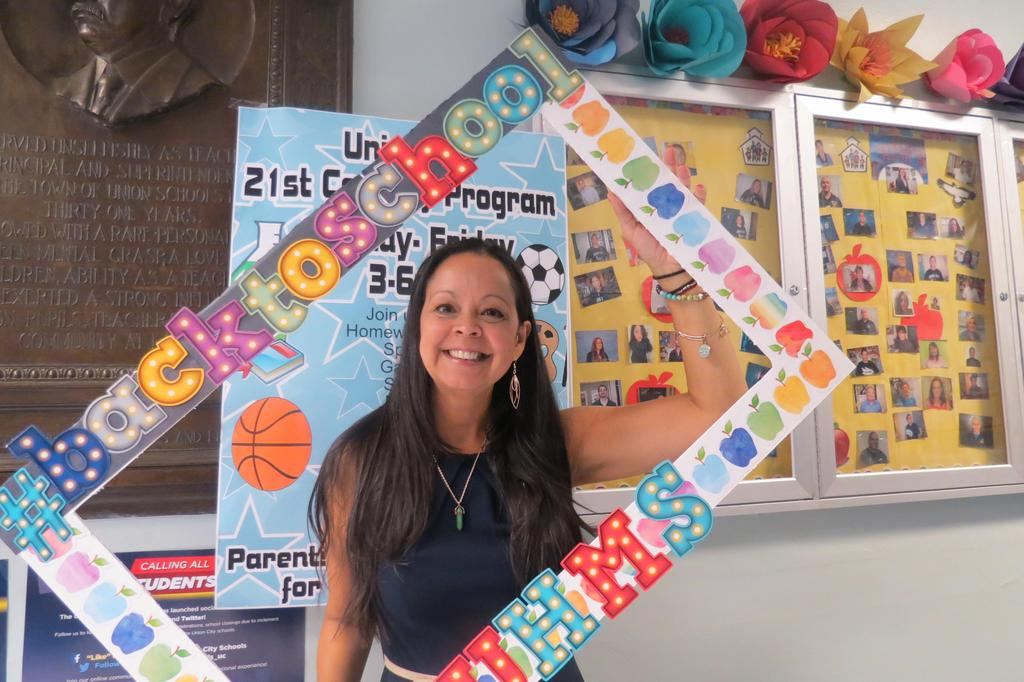 Ms. Garcia with a back to school photo board