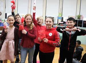 Photo of a group of McKinley School 5th graders showing off the prizes they won during a Valentine's Day game.