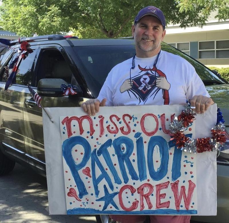 Liberty High School teacher holds sign in celebration of seniors.