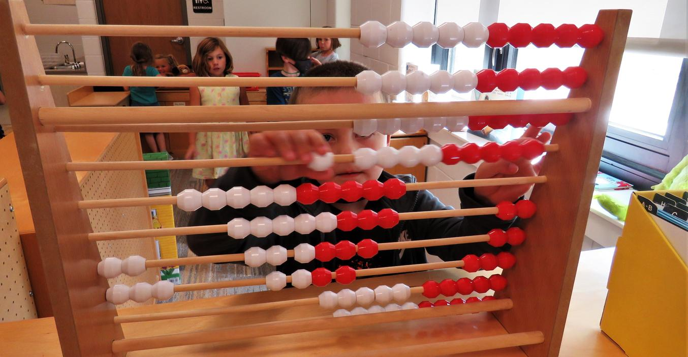 A McFall students plays with an abacus in his classroom.