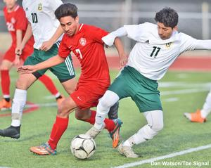 Photo by Dan Watson / The Signal. Photo of a boys Soccer game between Hart High School and Canyon High School. Boy in red jersey running next to boy in green and white jersey with a soccer ball between them, other athletes run in the background.