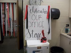 Office decorated with streamers and a sign.