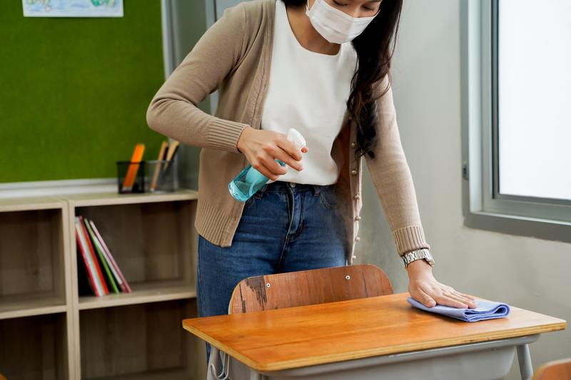 adult cleaning a classroom desk