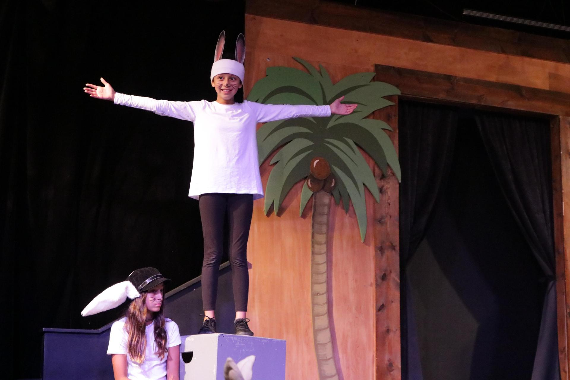 Sixth grader in a bunny costume stands on stage