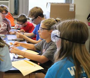CSI sleuths study clues to solve a crime during STEM Camp.