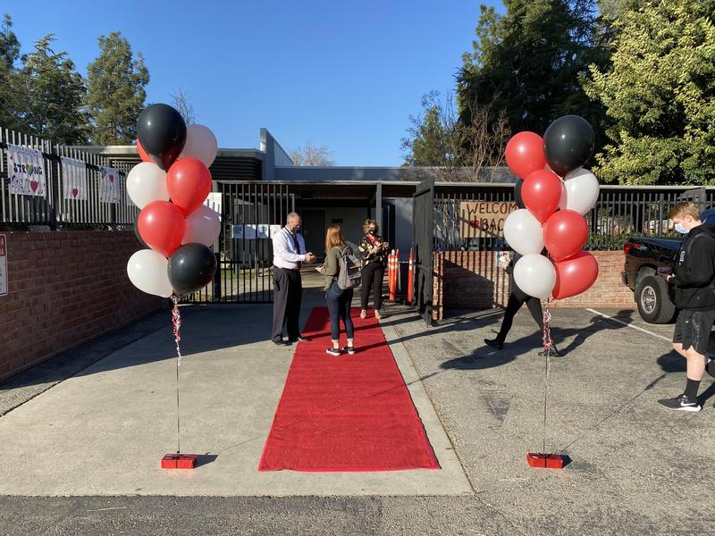 Hart High School rolled out the red carpet and red white and black balloons at the check-in gate for students lined up to be greeted by Principal d'Autremont