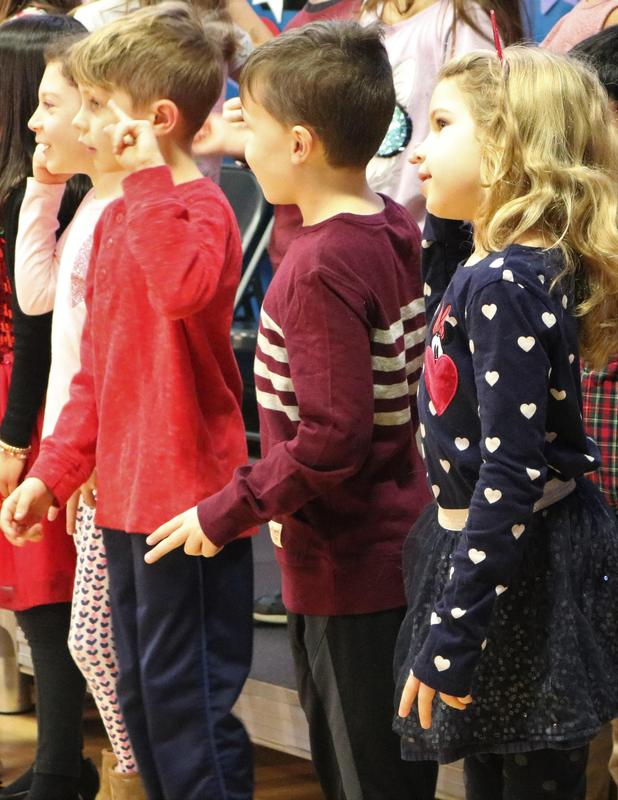 A photo of Washington School first graders as they enjoy performing during a Valentine's Day Singalong.