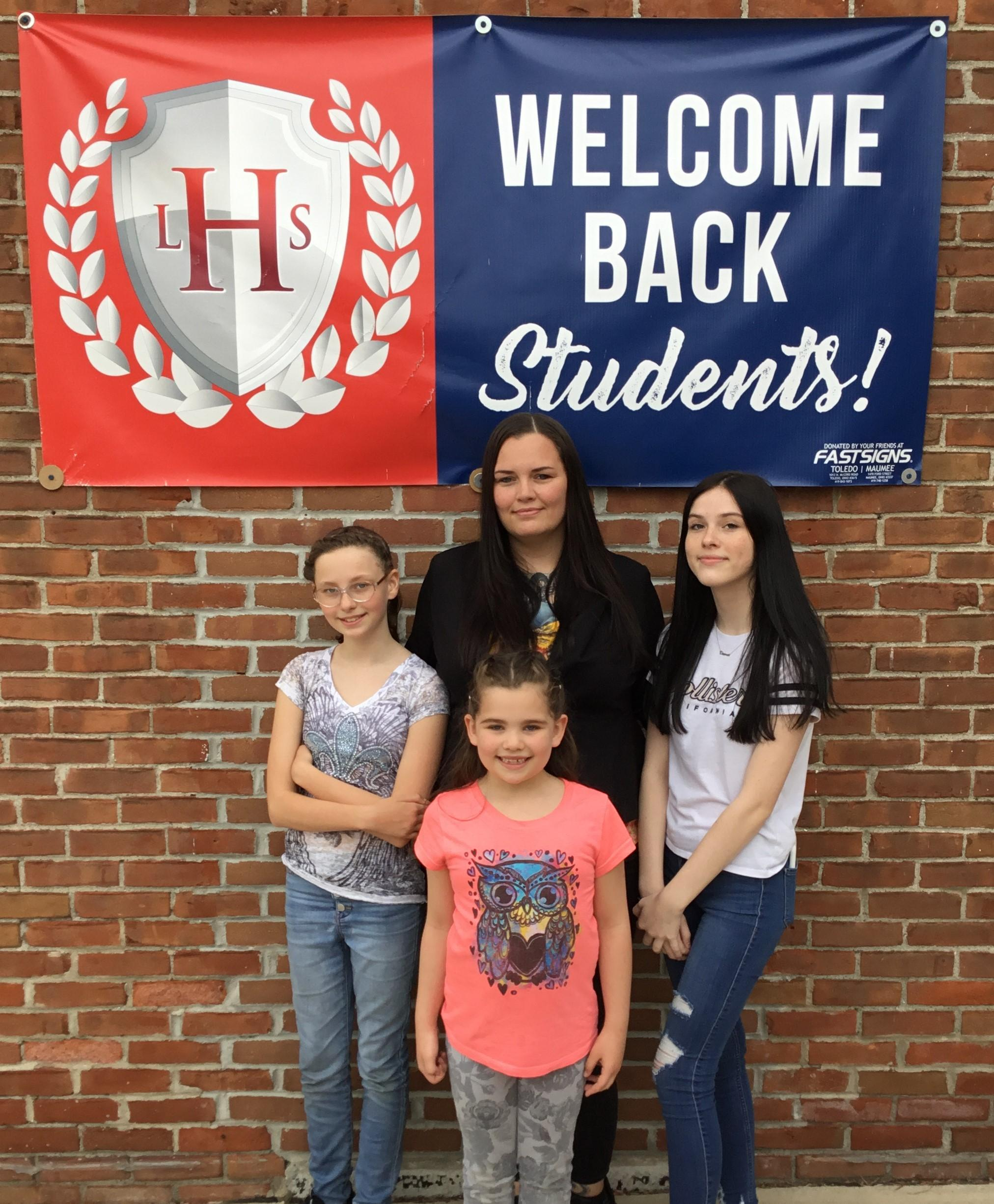 Picture of LHS family standing in front of our welcome sign.