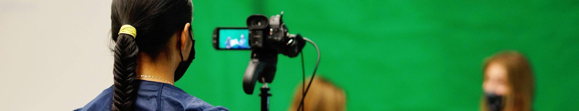 girls filming against a green screen
