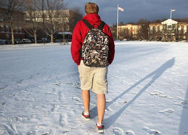 Boy Wearing shorts in the snow on way to class.