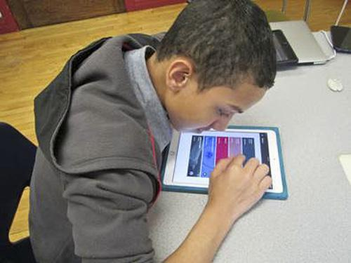 Misael working on his iPad with Google Classroom