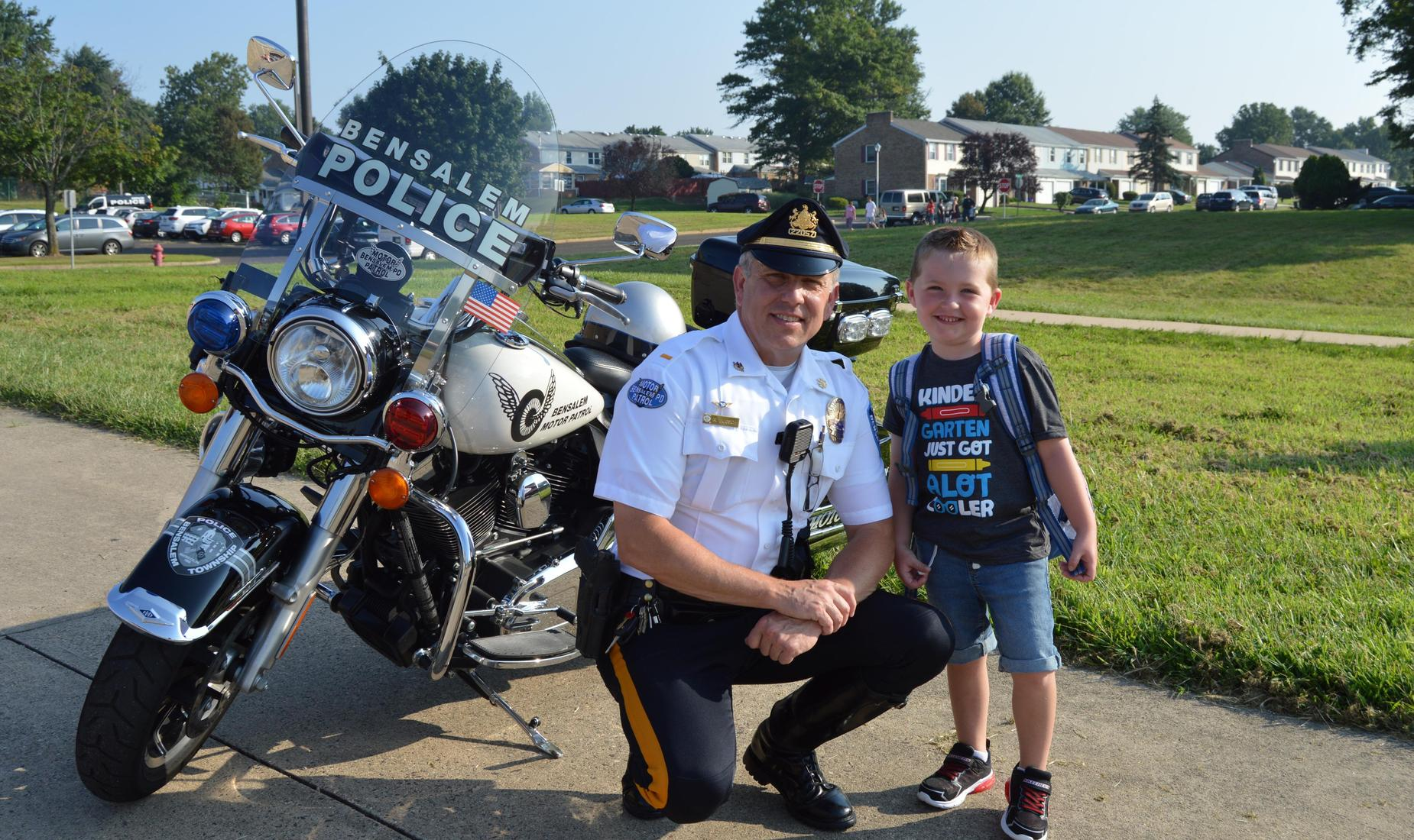 Bensalem Police Officer welcomes new students for the 2018-19 school year. Officer is posed with young boy in front of his motorcycle.